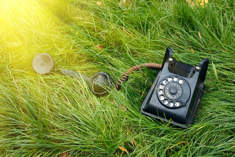 在草的黑老减速火箭的电话与阳光 图库摄影