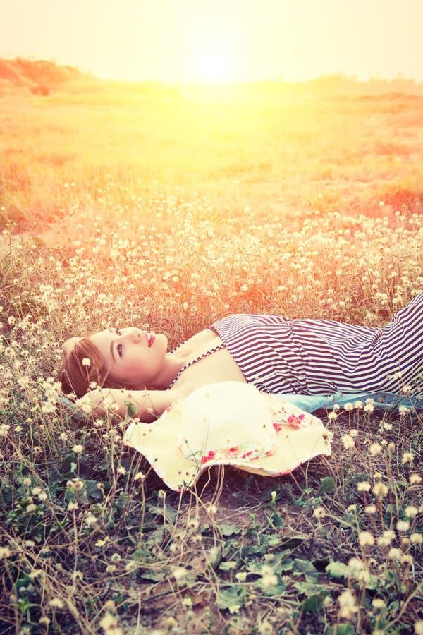 在草的年轻性感的妇女临近她的帽子神色入天空 库存图片