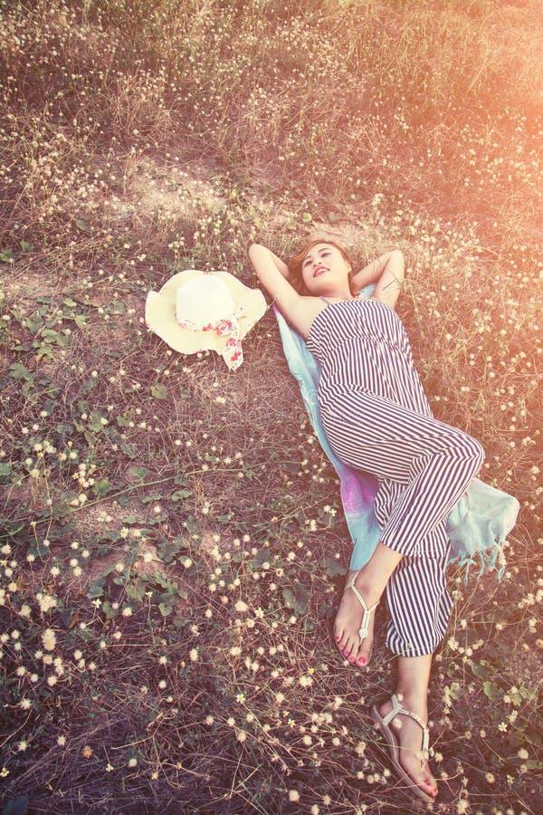 在草的年轻性感的妇女临近她的帽子 免版税库存图片