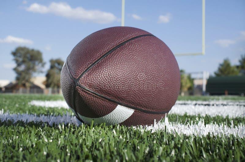 在草皮领域的橄榄球与目标岗位视线内 图库摄影