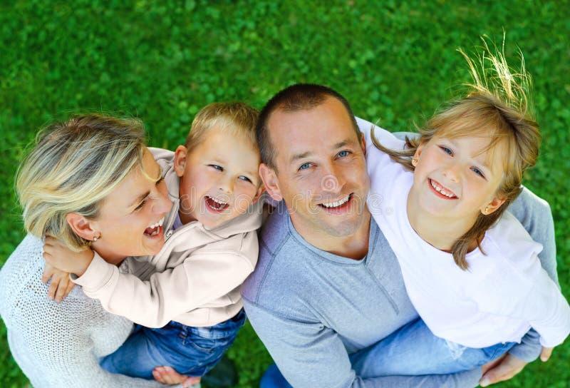 在草背景的愉快的家庭  图库摄影
