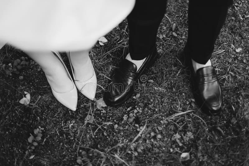 在草背景的新娘和新郎婚姻的鞋子  婚姻的细节,婚礼那天 r 免版税库存照片