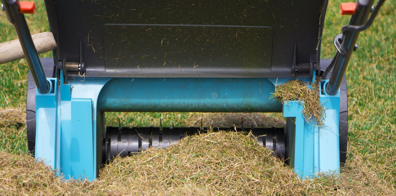 在草草坪的花匠运行的土壤通风机器 库存照片