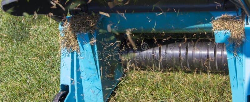 在草草坪的花匠运行的土壤通风机器 库存图片