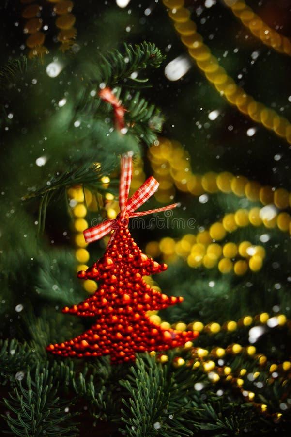 在草莓形状的圣诞节球在一个积雪的树枝的 有霜和雪花的红色玩具 选择聚焦 免版税图库摄影