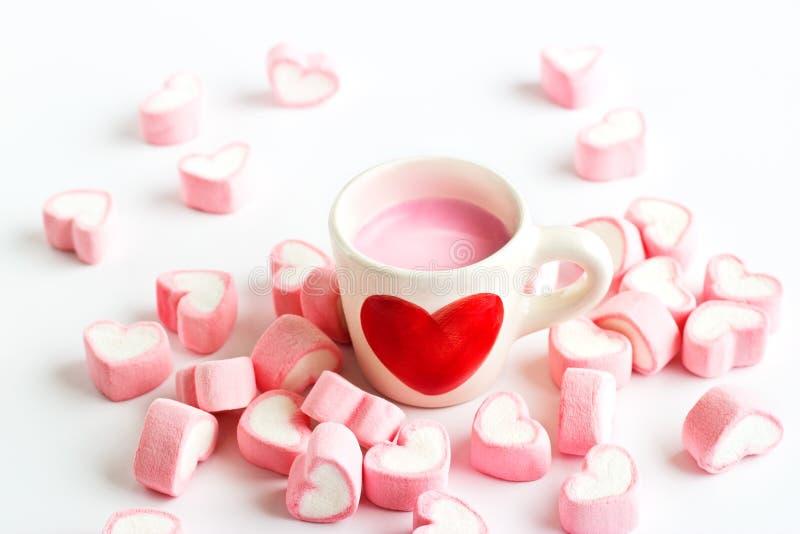在草莓牛奶杯子和桃红色糖果心脏的红色心脏标志 库存图片