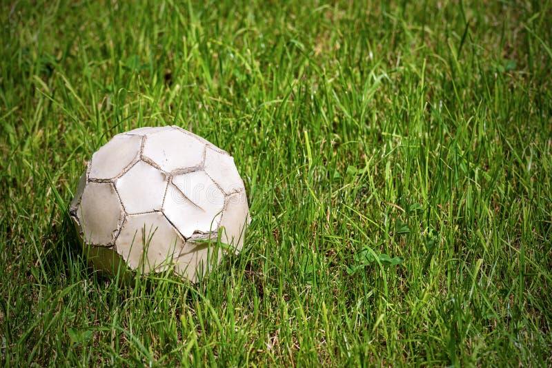 在草-橄榄球体育的老皮革足球 库存图片