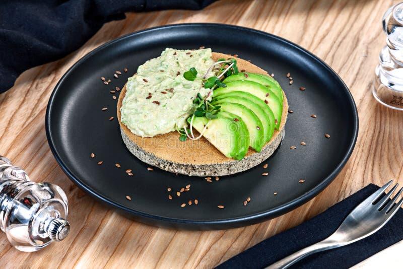 在荞麦面粉薄煎饼的接近的看法与在木背景的黑暗的板材从avacado的鳄梨调味酱捣碎的鳄梨酱供食的 健康,素食主义者 免版税库存照片