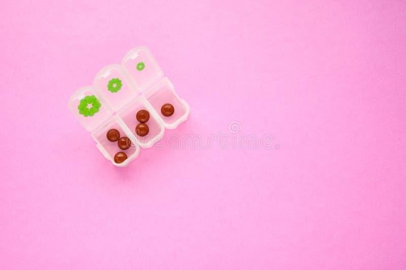 在药片箱子的布朗片剂在桃红色背景三的三天两一个在最左上侧 库存照片