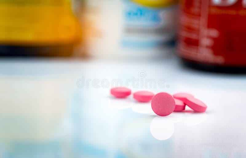 在药物瓶被弄脏的背景的圆的桃红色片剂药片  r 治疗偏头痛头疼的药物用途 免版税库存照片