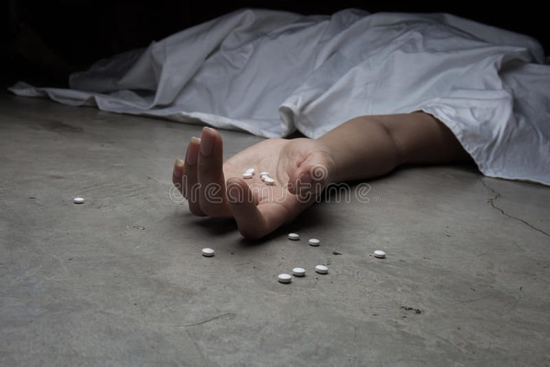 在药物的地板上的特写镜头在手中尸体 在 库存图片