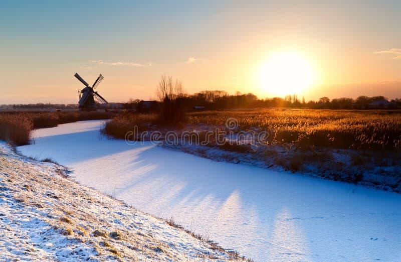 在荷兰风车和冻运河的日出 库存图片