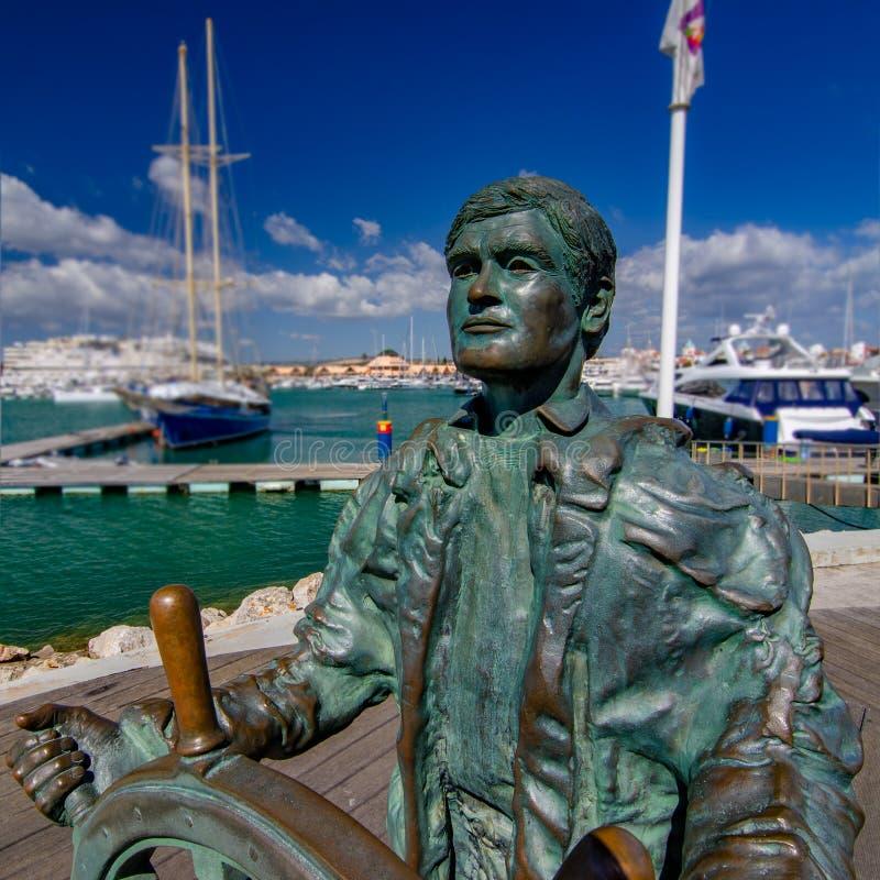 在莫拉镇小游艇船坞江边,葡萄牙的舵手雕象 图库摄影