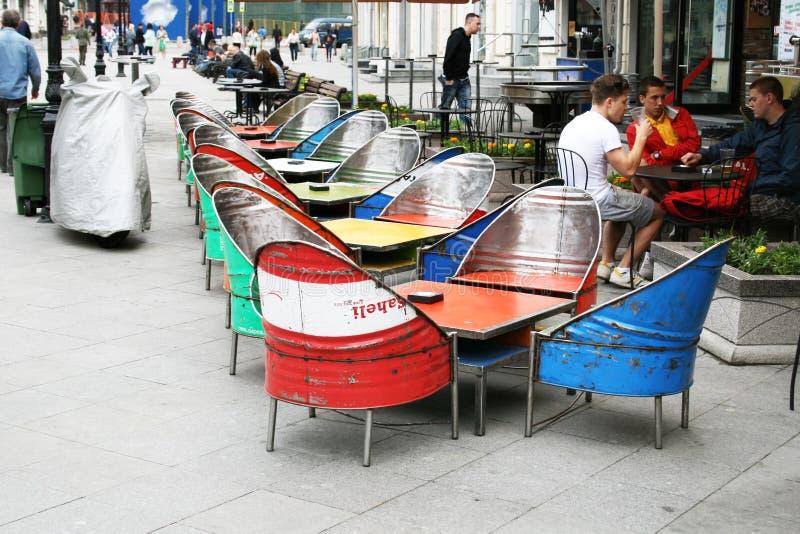 在莫斯科街道上的艺术咖啡馆有桌和椅子的由金属制成上色了桶 库存照片