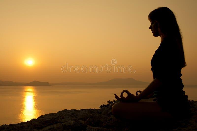 在莲花坐的凝思在日出在海边 免版税库存照片