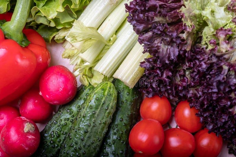 在莴苣一个轻的木桌、红色辣椒粉、芹菜、叶子,蕃茄樱桃、黄瓜和萝卜上的菜 免版税库存照片