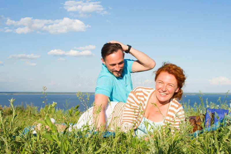 在获得乐趣和享用美好的自然和蓝天与云彩的爱的有吸引力的夫妇 微笑的和愉快的夫妇 免版税库存图片