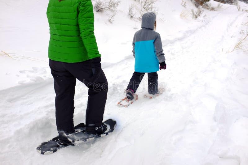 在获得冬天雪的孩子的家庭Snowshoeing乐趣 免版税库存图片