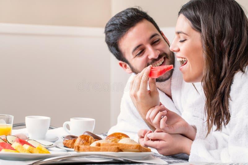 在获得的浴巾的夫妇吃果子的乐趣 免版税库存图片