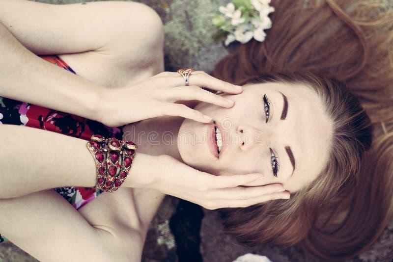 在获得美丽的白肤金发的小姐的特写镜头肉欲上微笑&看在夏天户外背景的乐趣照相机 库存图片