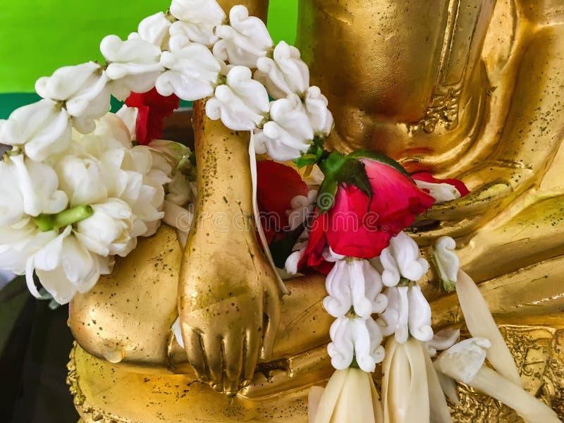 在菩萨雕象的手上的花卉诗歌选 免版税库存照片