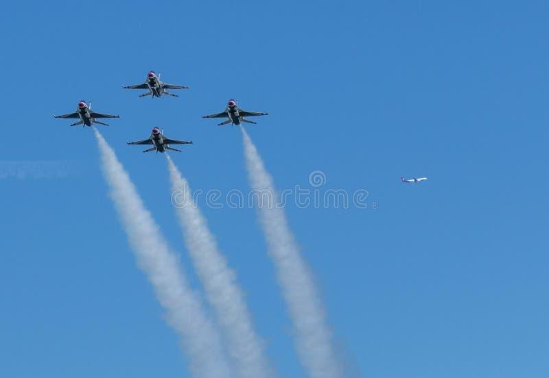在菱形队形的美国空军雷鸟与在距离的comertial飞机 库存照片