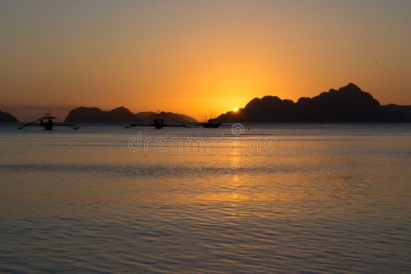 在菲律宾的风景日落有传统小船剪影的 与小岛的明亮的日落在背景 在海岸线的黄昏 免版税库存照片