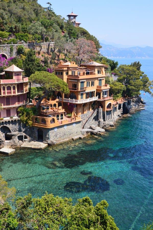 在菲诺港岸的美丽的别墅用地中海,菲诺港,意大利的清楚的绿色水 免版税库存照片