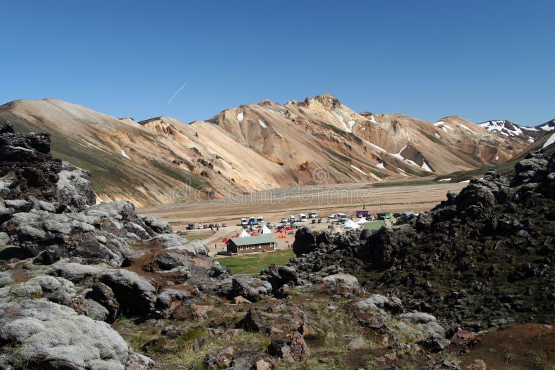 在营地的看法在坚固性山围拢的谷在兰德曼纳劳卡,冰岛 免版税库存图片