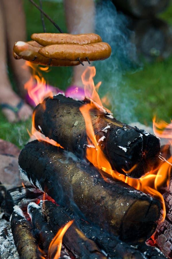 在营火的香肠在家庭菜园 免版税库存图片