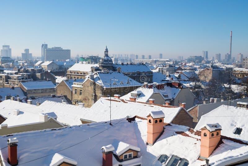 在萨格勒布有圆顶的和烟囱的全景视图在与雪在屋顶,萨格勒布,克罗地亚,欧洲的冬天期间 图库摄影