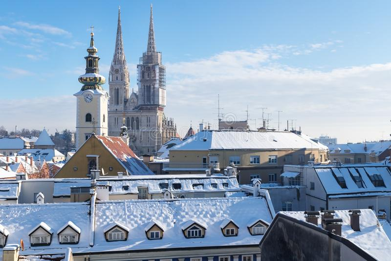 在萨格勒布的看法在与雪的冬天期间有对教会和大教堂,萨格勒布,克罗地亚,欧洲塔的细节视图  免版税库存照片