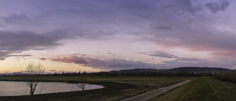 在萨格勒布镇的西边的全景有湖、树、道路在萨瓦河堤防和多云五颜六色的天空的在日落 免版税库存图片