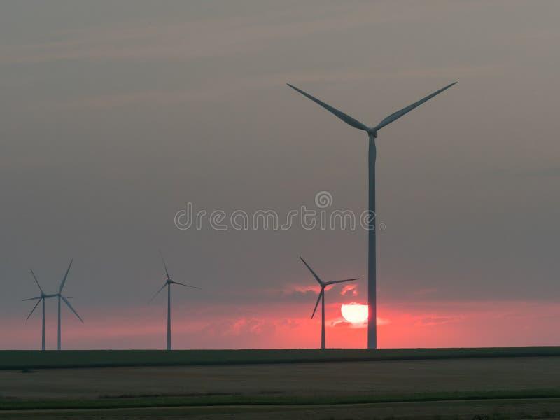 在落日的风轮机剪影 库存照片