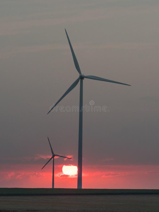 在落日的风轮机剪影 免版税库存图片