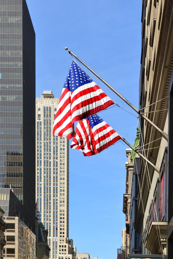 在著名摩天大楼背景的美国国旗在街市曼哈顿 E ?? 库存照片