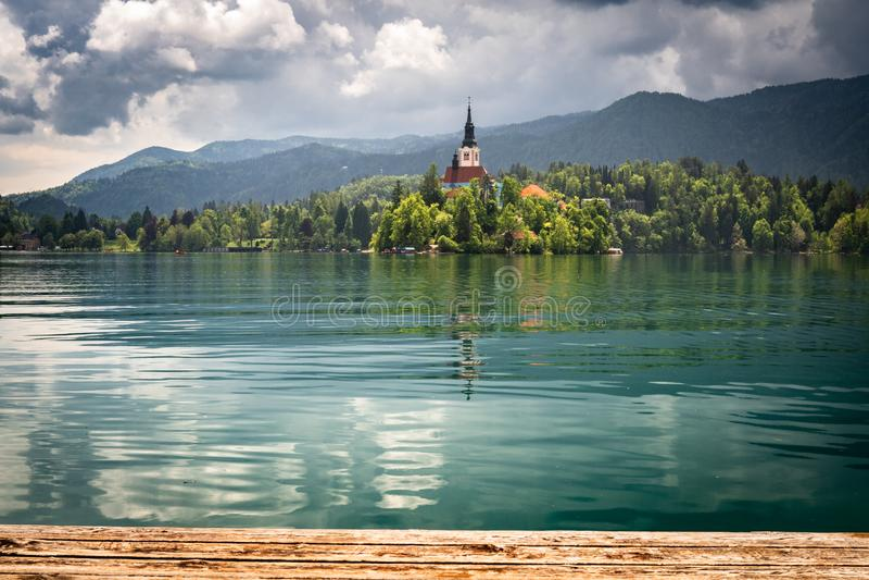在著名流血的湖的美丽的景色有在海岛上的教会的风雨如磐的天空的在朱利安阿尔卑斯,斯洛文尼亚 免版税图库摄影