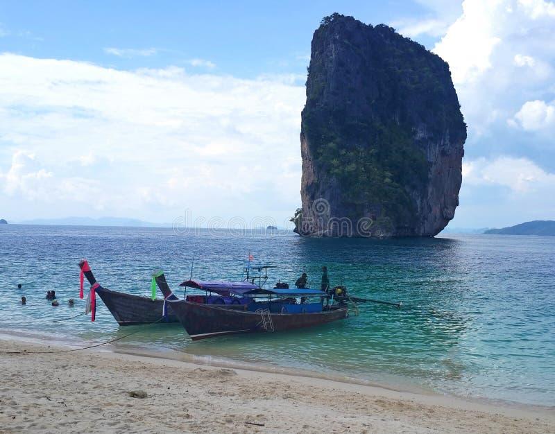 在著名热带白色沙子透明的绿色绿松石水的泰国longtail小船在Krabi,安达曼海,泰国靠岸 免版税库存图片