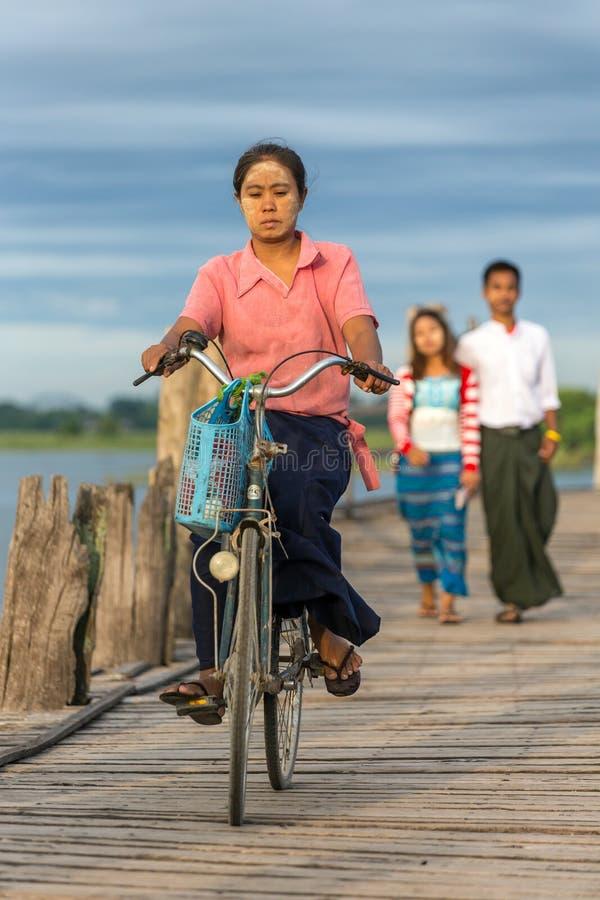 在著名U-Bein桥梁的未认出的缅甸妇女骑马自行车在曼德勒,缅甸附近的Amarapura 图库摄影