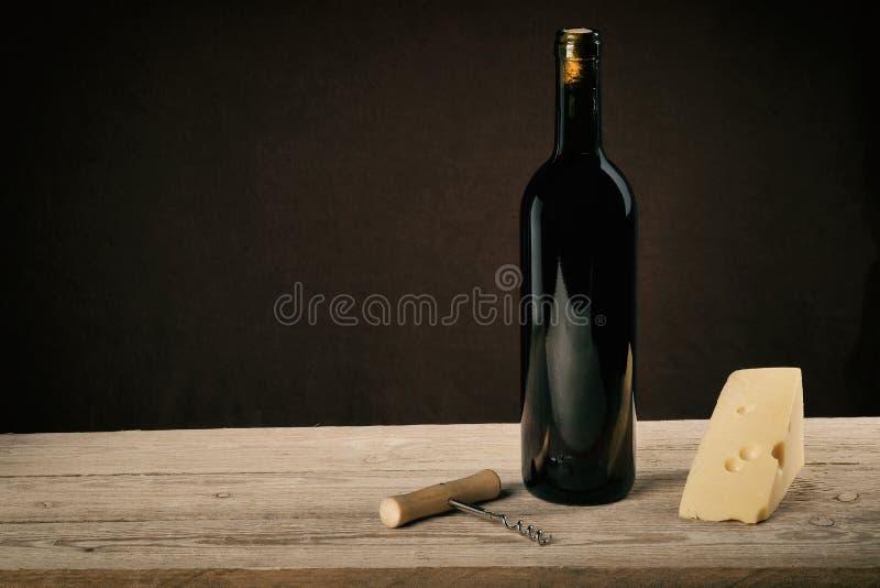 在葡萄酒光的红酒用乳酪和拔塞螺旋 库存照片