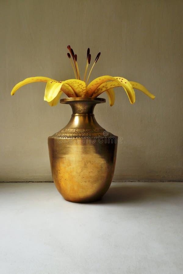 在葡萄酒印地安铜瓶子的黄色百合 免版税图库摄影