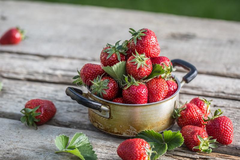 在葡萄酒厨房罐的新鲜的成熟草莓在老庭院桌上 免版税图库摄影
