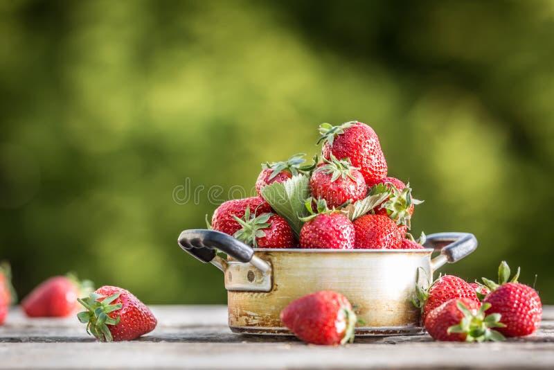 在葡萄酒厨房罐的新鲜的成熟草莓在老庭院桌上 图库摄影