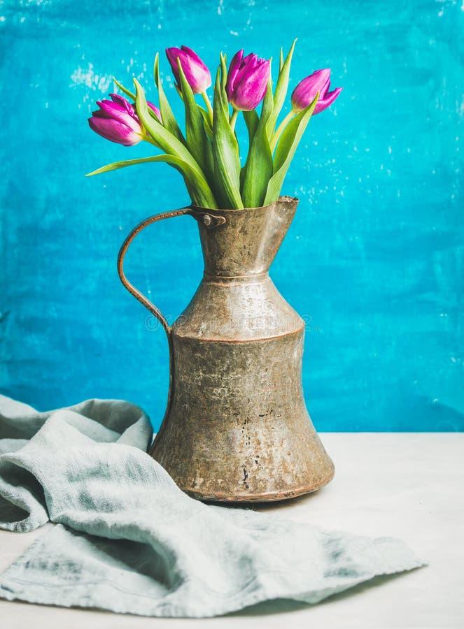 在葡萄酒土气铜水罐,蓝色墙壁的春天紫色郁金香 免版税库存图片