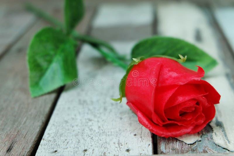 在葡萄酒地板上的红色玫瑰 库存照片