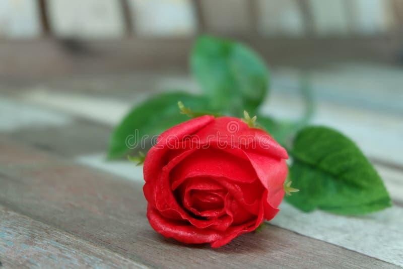 在葡萄酒地板上的红色玫瑰 库存图片