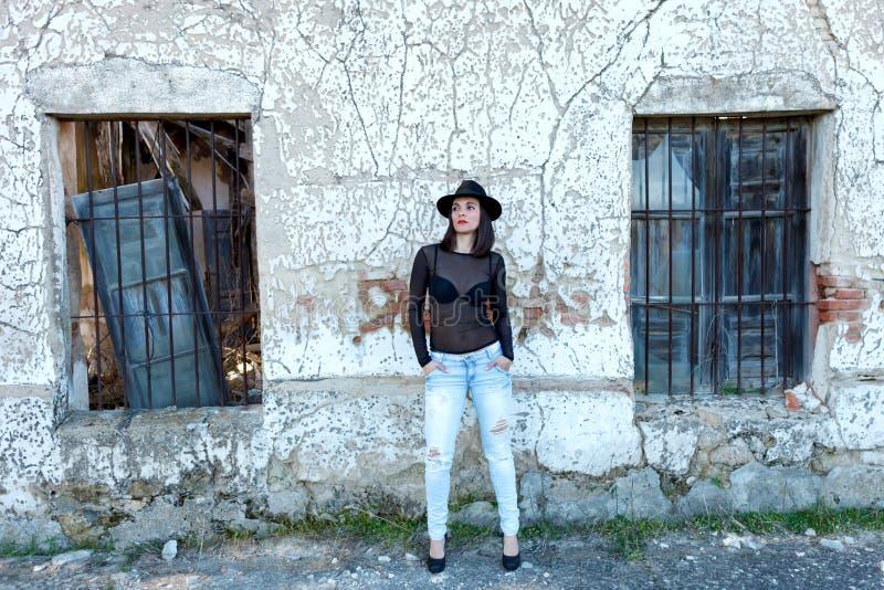 在葡萄酒房子前面的肉欲的妇女 免版税库存照片