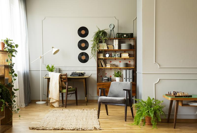 在葡萄酒时髦的内部的灰色舒适的扶手椅子与植物、书和乙烯基在墙壁上 库存图片
