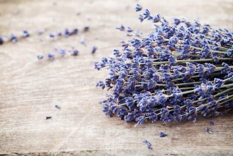 在葡萄酒木桌上的干燥淡紫色堆 土气样式 免版税库存照片