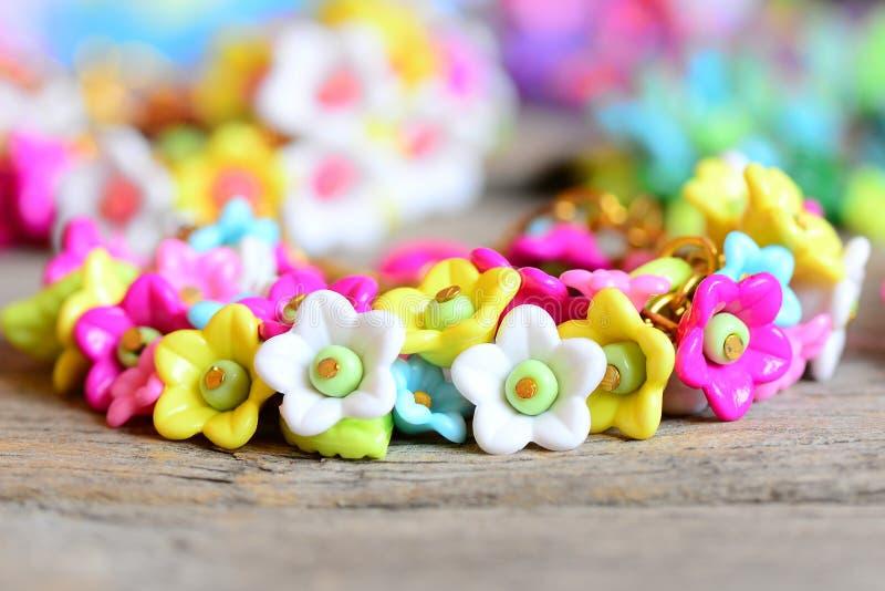在葡萄酒木桌上的漂亮的孩子镯子 镯子由五颜六色的塑料花、叶子和小珠做成 库存照片